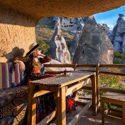 woman-bohemian-dress-sitting-traditional-cave-house-cappadocia-turkey